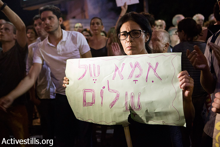 """A mother of an Israeli soldier serving in Gaza holds a sign reads: """"Mother of Peace"""" during a demonstration in center Tel Aviv against the Israeli attack on Gaza, August 2, 2014. Police arrested 17 left-wing protesters as hundreds gathered outside Habima Theatre to call for an end the attack on Gaza."""