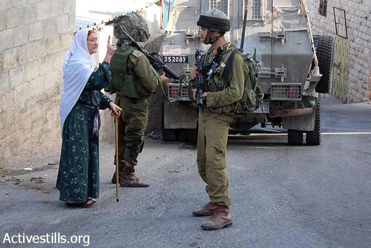 A Palestinian woman shouts at Israeli soldiers during an army operation in which soldiers killed Zakaria al-Aqra, 24, in the West Bank village of Qabalan, Nablus, West Bank, August 11, 2014. The Palestinian was wanted by Israel. Six other people from his family were wounded and parts of his house were destroyed during the operation which lasted for eight hours.