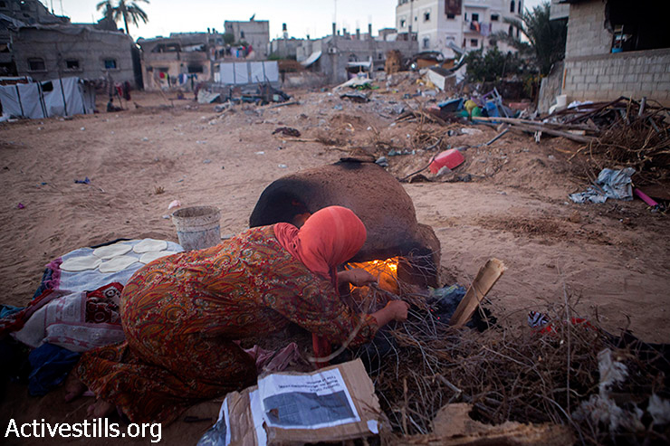 A Palestinian woman prepares bread in a tradionnal oven in the village of Khuza'a, eastern Gaza Strip, September 9, 2014. Khuzaa'a was heavily attacked and damaged during last Israeli offensive. Parts of the village were occupied by Israeli soldiers and out of reach of ambulances and the media during the offensive. As people were fleeing they were also attacked, and dozens were killed and many injured.