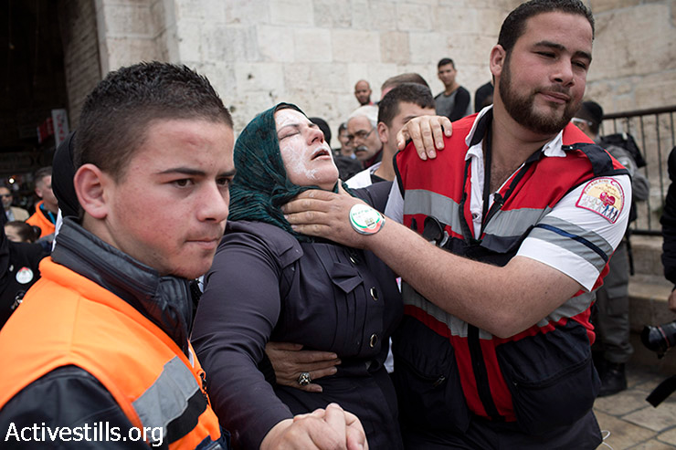 Palestinian medics evacuate a woman who was injured by pepper spray used by Israeli border policemen during a protest on Land Day outside of the Old City of Jerusalem, March 30, 2014. Land Day marks the deaths of six Palestinian protesters at the hands of Israeli police during mass demonstrations on March 30, 1976, against plans to confiscate Arab land in Galilee.