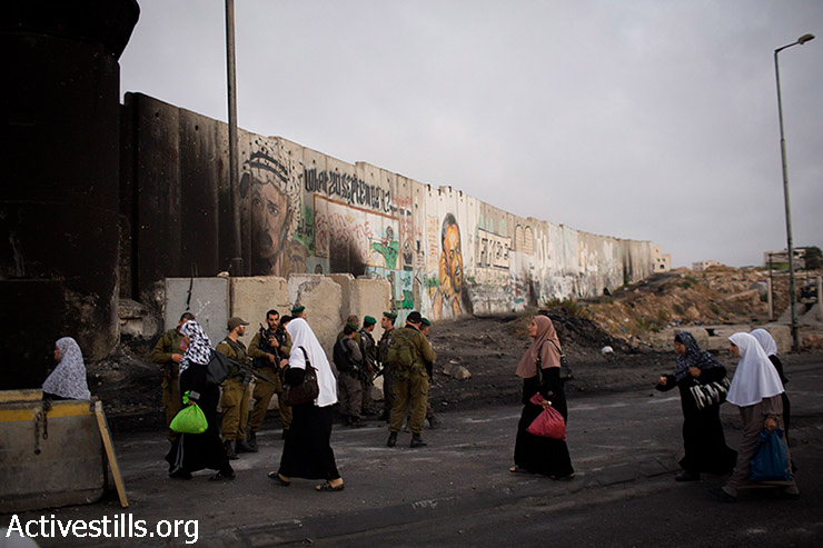 Palestinian women pass through Qalandiya checkpoint, near the West Bank city of Ramallah, on their way to attend the third Friday prayer of Ramadan in Al Aqsa Mosque, July 18, 2014.  Israeli authorities had forbidden access to Al-Aqsa mosque to Muslim men under 50 years old and for Muslim women under 40.