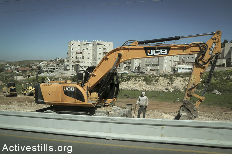 An Israeli bulldozer builds a wall between Jalazun refugee camp and the Jewish settlement Beit El, March 26, 2015. (photo: Ahmad al-Bazz / Activestills)