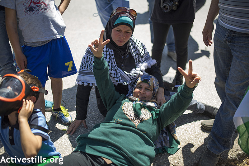 Manal Tamimi making a V sign after she was shot with life ammunition, during the weekly protest against the occupation, Nabi Saleh, West Bank, April 3, 2015. Anne Paq / Activestills.org