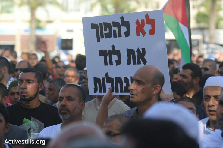 A man holds a sign that reads, 'Don't turn Lod into a settlement.' Thousands of Palestinian citizens of Israel demonstrate against the government's housing discrimination and policy of home demolitions, Rabin Square, Tel Aviv, April 28, 2015. (Oren Ziv/Activestills.org)
