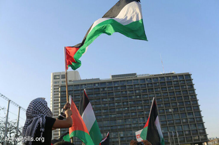 Palestinian flags wave in front of Tel Aviv City Hall at a demonstration against the government's housing discrimination and policy of home demolitions, Rabin Square, Tel Aviv, April 28, 2015. (Oren Ziv/Activestills.org)