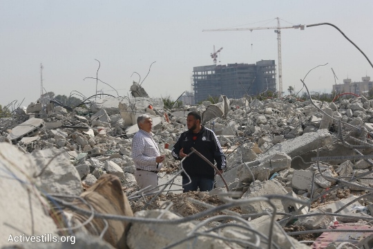Residents walk through the remains of their homes in the unrecognized village Dahmash, Israel, April 15, 2015. (Oren Ziv/Activestills.org)