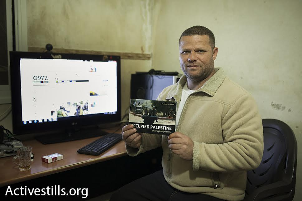 Palestinian photographer Haitham Khatib holds a copy of his book 'Occupied Palestine Through My Lens.' (photo: Oren Ziv/Activestills.org)