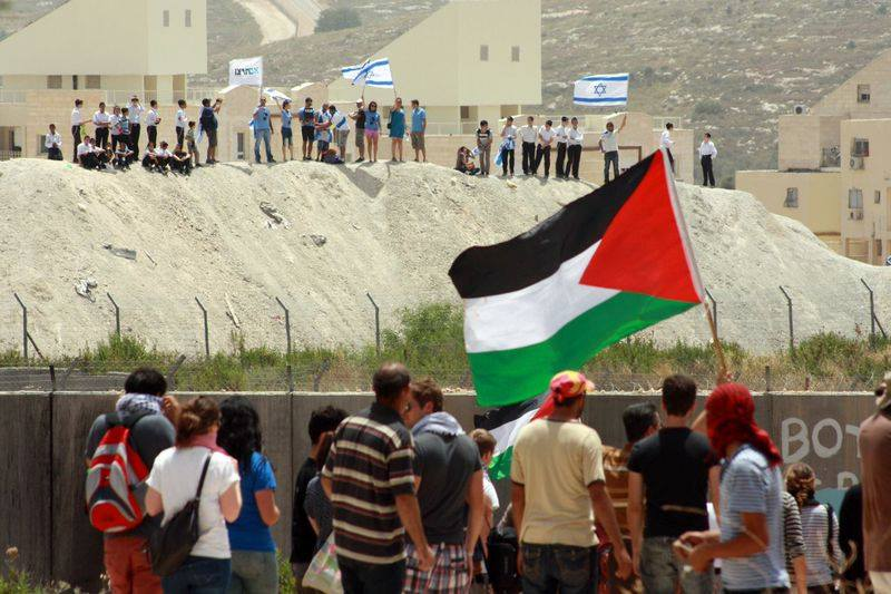 Palestinian protesters in Bil'in look beyond the separation wall at settlers from the Modi'in Illit settlement bloc. (photo: Haithem Khatib)