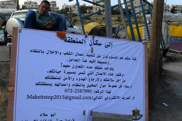 A sign posted by the IDF in the West Bank village Hizma calls on residents not to cooperate with those 'responsible for carrying out riots and disturbances of the peace,' and asks that they report on those behind the disturbances. (photo: Tamar Fleishman)