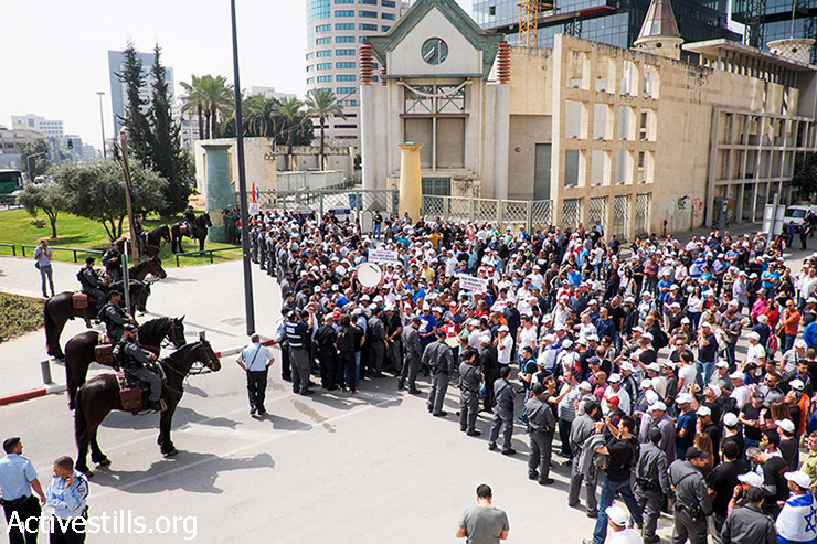 Israeli workers  confront police during a protest against the plan to dismiss hundreds of workers employed in a factory of the CIL group, in front of the company offices in Tel Aviv on March 10, 2015. (photo: Activestills.org)