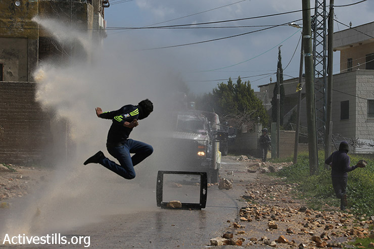 A Palestinian youth jumps as a water canon sprays water during clashes with the Israeli army at the weekly protest against the occupation, Kafr Qaddum, West Bank, March 13, 2015. Locals began to organize demonstrations in July 2011 to protest the blocking of the main road linking Kafr Qaddum to Nablus. (photo: Activestills.org)
