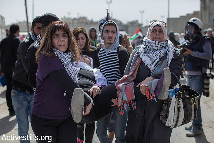 A Palestinian woman is evacuated after she was injured during a demonstration against the occupation one day before International Women's Day, in front of Qalandiya checkpoint, West Bank, March 7, 2015. The annual march was repressed by the Israeli army. (photo: Activestills.org)
