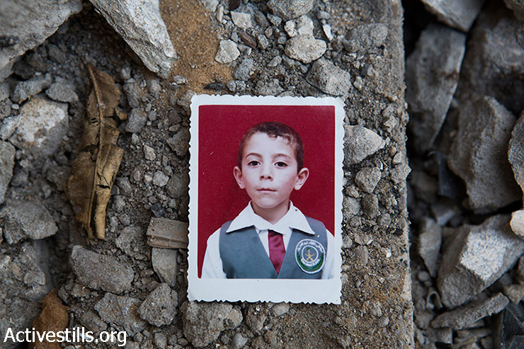 A photo of Abdallah Abdel Hadi Al Majdalawi lies amid the ruins of his home, Gaza Strip, March 19, 2015. Abdallah (13) was killed alongside his brother Abdelrazek (19) and his cousins Rawan (9) and Mahmoud (8), by an Israeli attack which occured without prior warning on August 3, 2014. The attack destroyed also the adjacent home of Ahmed Al Majdalawi.  (photo: Activestills.org)