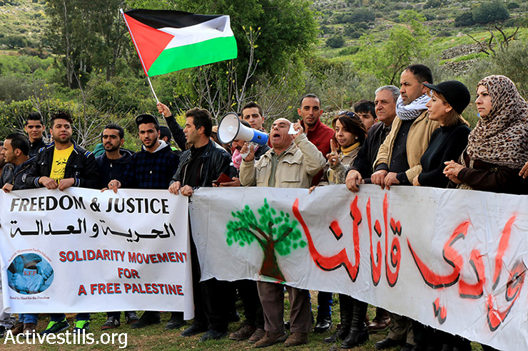 "Palestinian and international activists hold a sign that reads, ""Wadi Qana is for us"", during a solidarity activity with Palestinian farmers in the area, West Bank, March 20, 2015. On Sunday March 15, Palestinians received an Israeli military order to uproot 123 olive trees in Wadi Qana, which is surrounded by seven settlements. If the Israeli Separation Wall is built as planned, the land of Wadi Qana will be confiscated on the ""Israeli"" side. (photo: Activestills.org)"