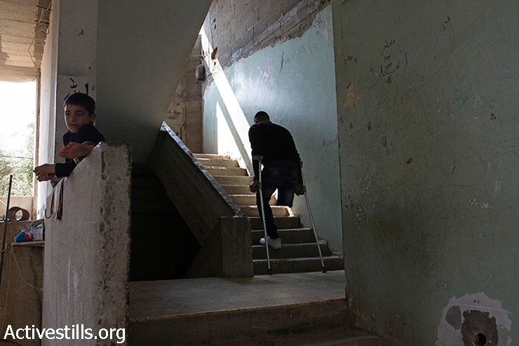 Wael al-Namlah, 26, climbs the stairs in his home in Rafah, Gaza Strip, March 18, 2015. Members of the al-Namlah family were fleeing Israeli attacks on August 1, when they were targeted by two missiles some 600 meters from their home. Three members of the family were killed: Youssef (Wael's brother), his wife Wala, and 11-year-old Angham (Wael's sister). Wael was injured alongside his wife, Israa, who lost her legs and their 3-year-old son Shereef, who lost the lower part of his left leg. Six months after the 2014 Israeli offensive on Gaza, 100,000 Palestinians are still displaced. (photo: Activestills.org)
