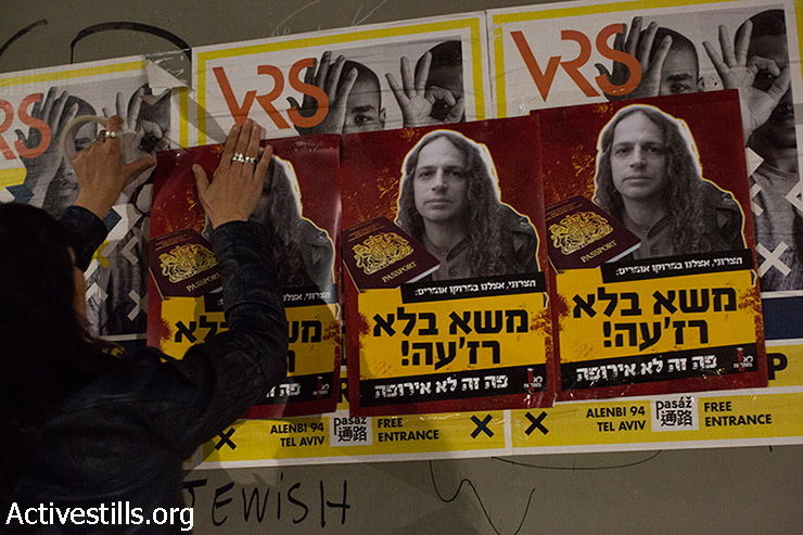 A Mizrahi activist hangs a sign against Amit Hetzroni, following racist announcements he made against Mizrahi Jews, Tel Aviv, Israel, March 23, 2015. (photo: Activestills.org)