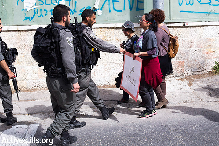 An Israeli policeman confiscates a sign from a protester during a demonstration against the Judaization of East Jerusalem, March 27, 2015. (photo: Activestills.org)