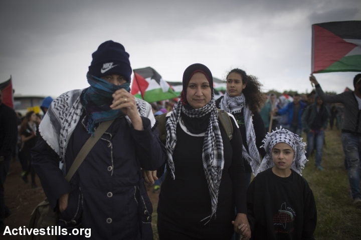 A Palestinian family marches in the heavy rain as thousands of Palestinian citizens of Israel take part in the 'March of Return,' on the land belonging to the destroyed village of Hadatha, near Tiberias, April 23, 2015. (photo: Oren Ziv/Activestills.org)