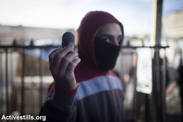 A Palestinian youth displays a block sponge-tipped bullet shot by Israeli police near the Shuafat Refugee Camp in East Jerusalem, November 7, 2014. (Photo by Oren Ziv/Activestills.org)