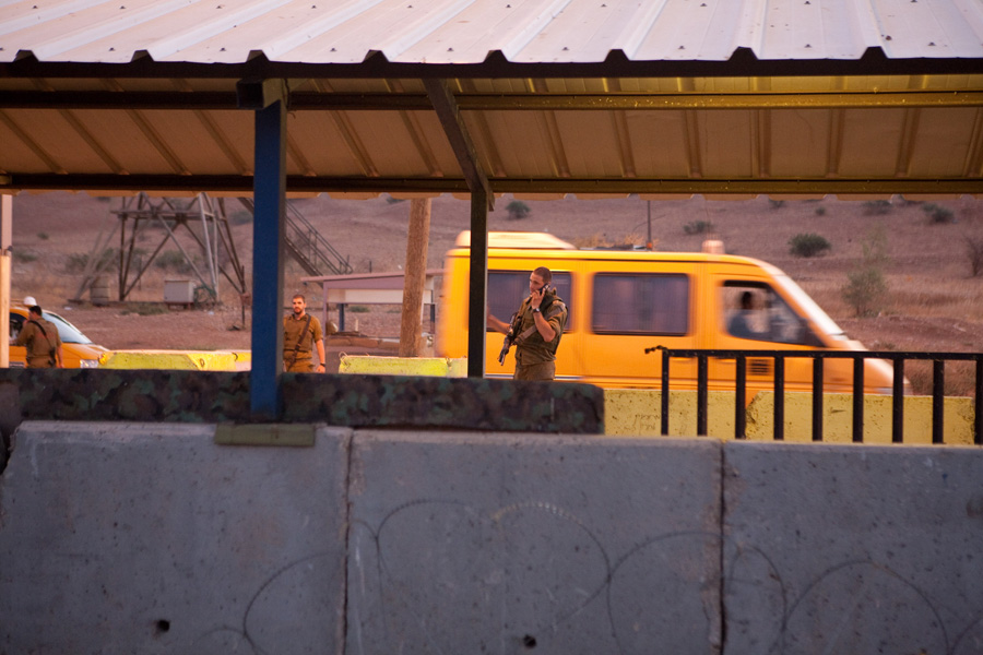 A Palestinian service taxi passes through an Israeli army checkpoint in the West Bank. (Activestills.org)