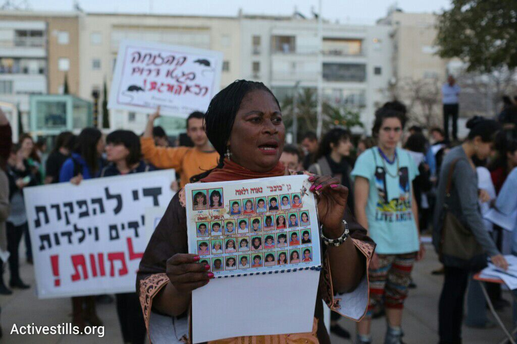 A woman holds up a photo of a refugee daycare center's yearbook during a protest against living conditions in south Tel Aviv, April 19, 2015. Five refugee children have recently died due to the substandard living conditions in daycare centers. (photo: Oren Ziv/Activestills.org)