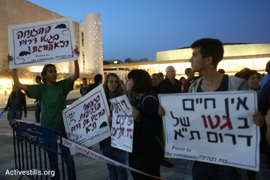 "Protesters wave signs during a demonstration against the poor living conditions in south Tel Aviv, April 19, 2015. Sign (right): ""There is no life in the ghetto of south Tel Aviv."" (photo: Oren Ziv/Activestills.org)"