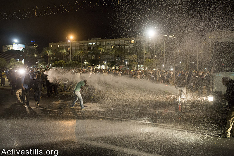 Police sprays protesters with coloured water during an Israeli Ethiopian protest against police brutality and racism, Tel Aviv, May 3rd, 2015. Oren Ziv / Activestills.org