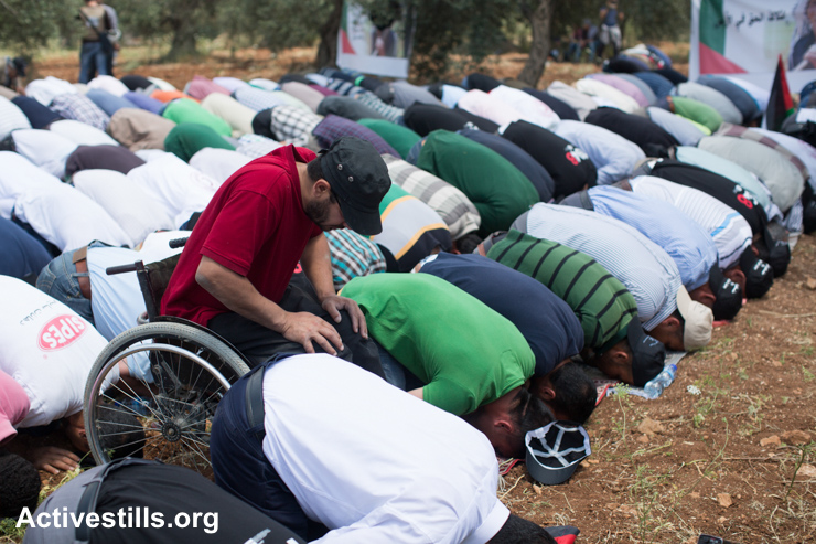 Palestinians pray during a protest against the Israeli Separation Wall that also marks Nakba Day, Nil'in, West Bank, May 15, 2015.