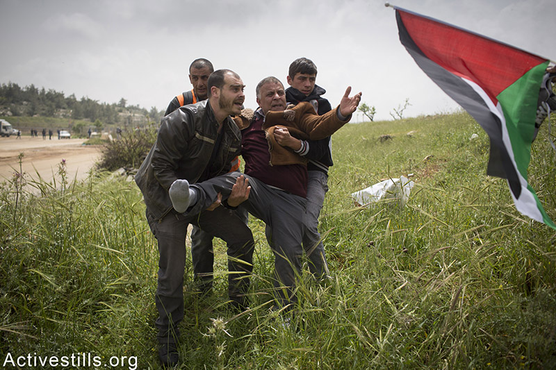 Protesters carry Palestinian man injured during a protest marking Palestinian prisoners day, outside the Ofer military prison, near the West Bank town of Betunia, April 16, 2015. Oren Ziv / Activestills.org