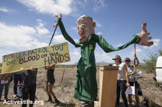 Activists with giant puppets perform political theater during a protest at the Amada checkpoint, Arizona, as part of a day of action against the militarization of the borderlands in Arizona, May 27, 2015. (Activestills)
