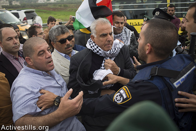 Israeli policemen push Palestinian protesters, including minister Walid Assaf, near the West Bank village of Sinjel during a protest against the closure road 60 between Ramallah and Nablus, as Jewish settlers organised a marathon under the name marathon in the West Bank, on April 9, 2015. Israeli police closed road 60 for over 6 hours, preventing from thousands of Palestinians from using it. Oren Ziv / Activestills.org