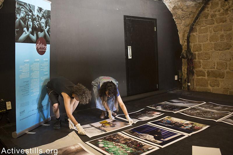 Activestills members hang photo exhibition 'Summer 2014' featuring photos from the Gaza war, in Jaffa theatre, April 29, 2015. Oren Ziv / Activestills.org