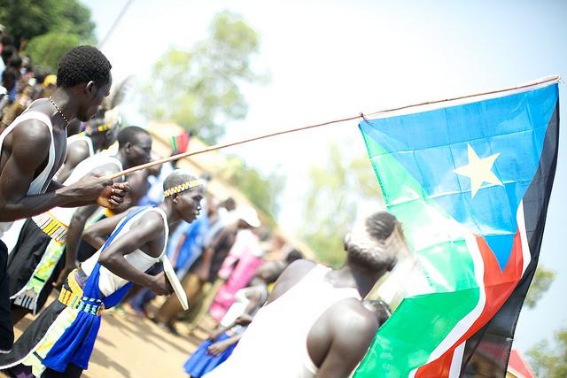 A man waves the South Sudan flag. (photo: Arsenie Coseac/CC BY-SA 2.0)