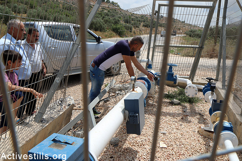 Palestinian checks the main water valve, now almost closed by Israeli authorities, in Qarawat Bani Hassan village, near Salfit, West Bank, May 23, 2015. According to the municipal council of Qarawat Bani Hassan the portion of a each villager has decreased to two litters per day as the village receive only 97 Cubic meter per hour. The municipal council said the Israeli authorities did not provide the village with answers regarding the situation. Ahmad al-Bazz / Activestills.org