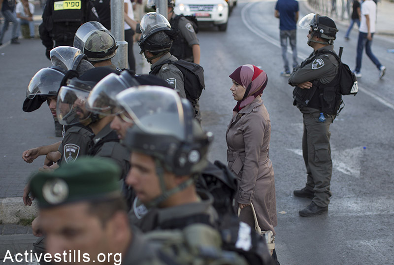 """A Palestinian woman stands near a police checkpoint outside Jerusalem's Old City, during the Jerusalem Day march, May 17, 2015. The march marks 48 years since the """"reunification"""" of the city. Activestills.org"""