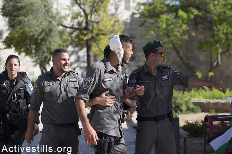 An injured border policeman is helped by his friends outside Jerusalem's old city, as Palestinians they protest against the flags march, May 17, 2015.The march marks 48 years for the occupation of East Jerusalem.