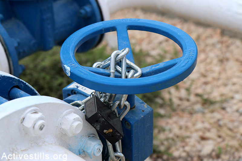The main water valve of Qarawat Bani Hassan village, near Salfit, is seen almost blocked by Israeli authorities limiting the water supply to the village and nearby villages, West Bank, May 23, 2015. According to the municipal council of Qarawat Bani Hassan the portion of a each villager has decreased to two litters per day as the village receive only 97 Cubic meter per hour. The municipal council said the Israeli authorities did not provide the village with answers regarding the situation. Ahmad al-Bazz / Activestills.org