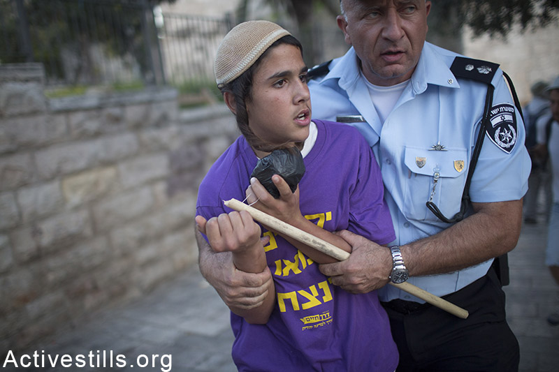 An Israel policeman detains an Israeli youth after he attacked Palestinian journalists outsideJerusalem's old city, during the flags march, marking 48 years for the occupation of East Jerusalem May 17, 2015.