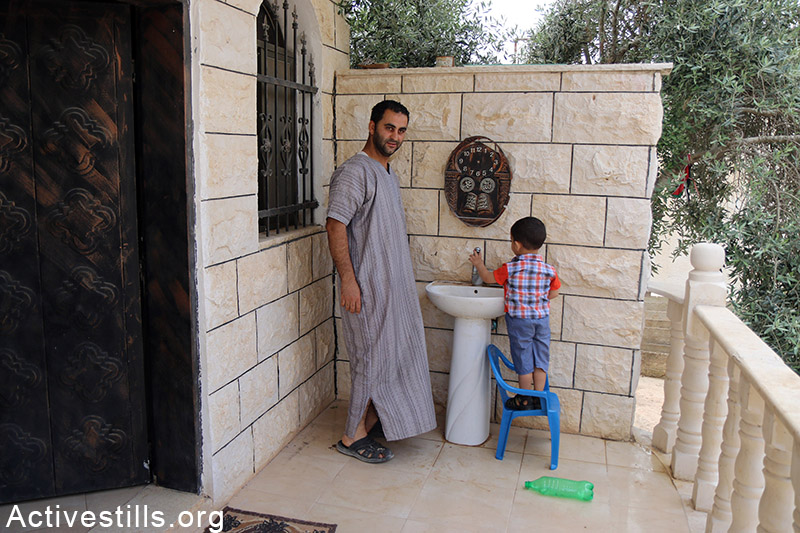 Palestinians check tap water volume in Qarawat Bani Hassan village, West Bank, May 23, 2015. According to the municipal council of Qarawat Bani Hassan the portion of a each villager has decreased to two litters per day as the village receive only 97 Cubic meter per hour. The municipal council said the Israeli authorities did not provide the village with answers regarding the situation. Ahmad al-Bazz / Activestills.org