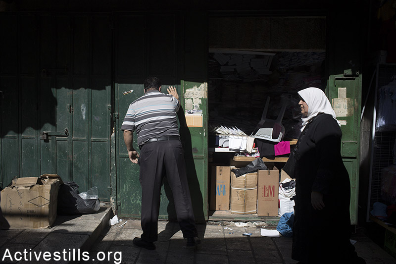 """A Palestinian shop owner closes his shop in Jerusalem's Old City before Jewish marchers pass by, May 17, 2015. The so-called """"flags march"""" marks 48 years since the """"reunification"""" of Jerusalem. Activestills.org"""