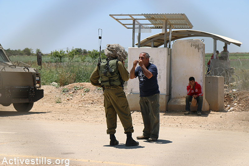 A Palestinian farmer argues with an Israeli soldier on the western side of the separation fence in Falamya village, West Bank, May 17, 2015. Ahmad al-Bazz / Activestills.org