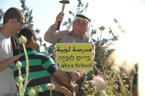 Representatives of Lubyan refugees place a sign indicating where the school once stood amid the ruins of the destroyed Palestinian village of Lubya, May 1, 2015. (Sarah Levy)