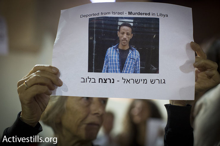An Israeli activist holds a photo of an Eritrean asylum seeker who was executed by Islamic State militants in Libya after being deported by Israel to a third country, Tel Aviv, May 2, 2015. (Photo by Oren Ziv/Activestills.org)