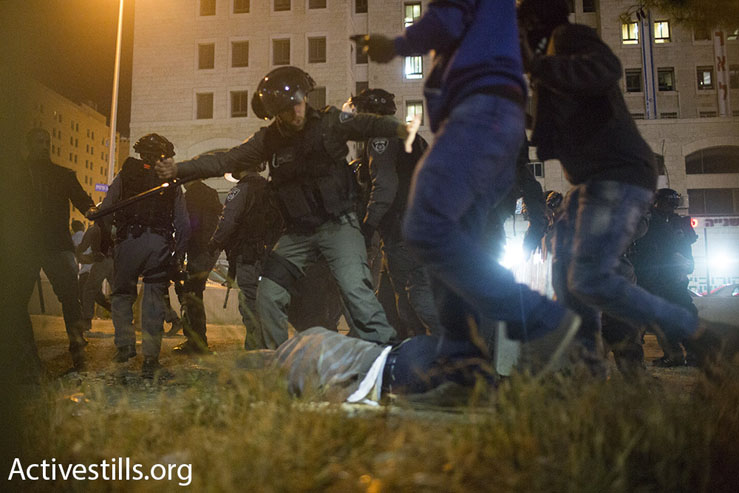 A police officer appears to use his baton against a protester lying on the ground at a demonstration against police brutality, Jerusalem, April 30, 2015. (Oren Ziv/Activestills.org)
