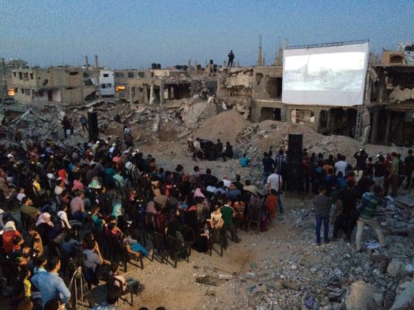 A film is shown on the screen built out of the wall of a destroyed home at the Karama Gaza Film Festival, Shujaiyeh neighborhood of Gaza City, May 13, 2015. (Photo by Dan Cohen)