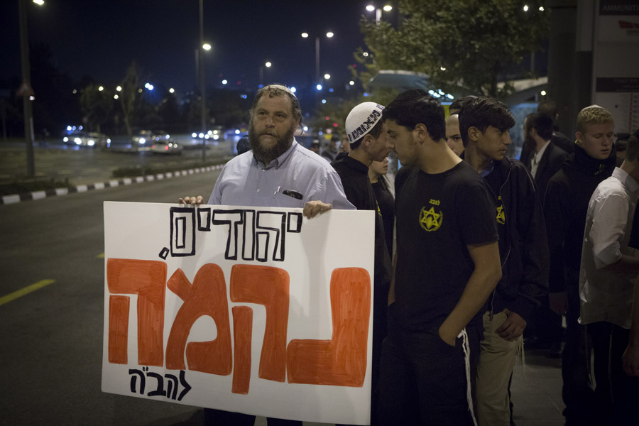Israeli right-wing activist Benzi Gopstein, leader of the Lehava organization, takes part in a protest near the tram station in East Jerusalem, a day after a Palestinian man killed a baby in a vehicular attack at the same location, October 23, 2014. The sign reads: 'Jews, Revenge'