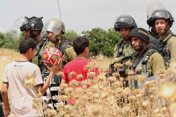 Palestinian children with Israeli soldiers during the weekly demonstration in Nabi Saleh, May 29, 2015. (Natasha Roth)