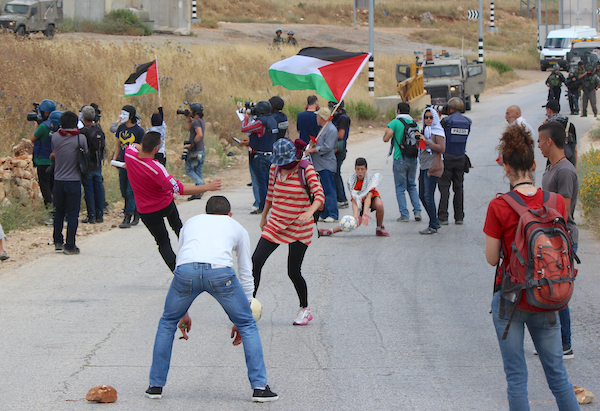 Palestinians and internationals play football, marking a vote to expel Israel from FIFA that was expected to take place later in the day. The game formed part of the weekly demonstration in Nabi Saleh, May 29, 2015. (Natasha Roth)