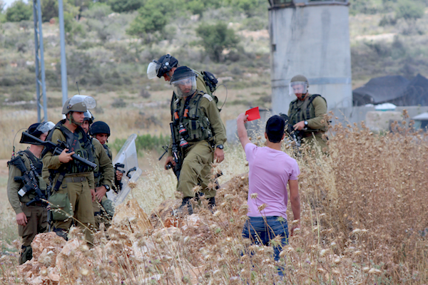 A Palestinian demonstrator shows Israeli soldiers the red card during the weekly demonstration in Nabi Saleh, May 29, 2015. (Natasha Roth)