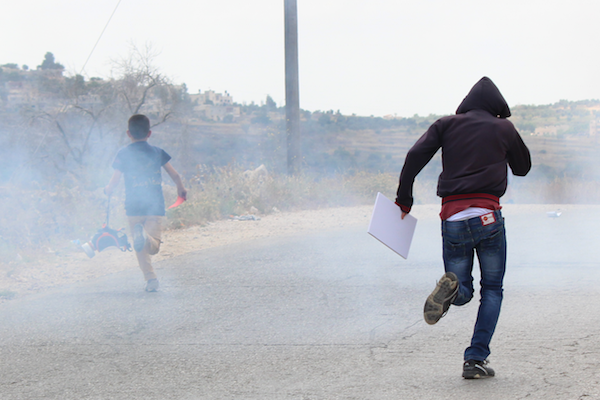 Palestinians children run from tear gas fired by the Israeli army in Nabi Saleh, May 29, 2015. (Natasha Roth)